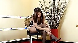 Glam shemale in stockings and high heels strokes her rod